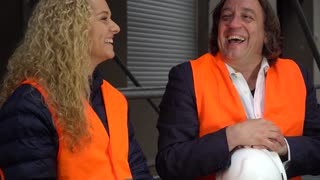 Male and female construction workers sitting on scaffolding and laughing together