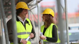 Male and female engineers talking at a construction site