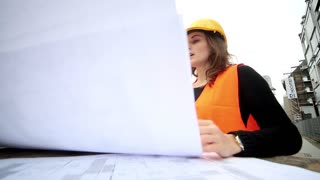 Male and female engineers talking on a construction site
