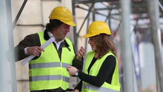 Male and female engineers with helmets talking on a construction site