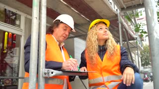 On construction site senior engineer explaining his young blonde trainee some projects