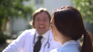 Profiled Asian nurse talking with her senior doctor colleague. Selective focus