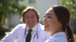 Profiled smiling Asian nurse talking outdoors with a male doctor