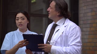 Senior doctor explaining young Asian trainee medical results