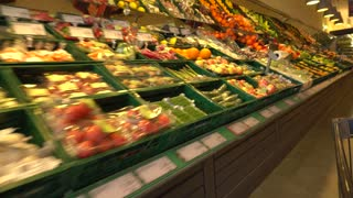 Shopping cart in supermarket among fruit and vegetable. Shopping cart point of view