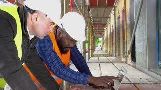 Side view: two architects, a black and a white, wearing safety jackets, helmets and goggles discussing looking at the computer among scaffolding