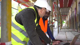 Side view: two engineers, a black and a white, wearing safety jackets, hardhats and goggles, discussing pointing at something on the computer desktop among scaffolding