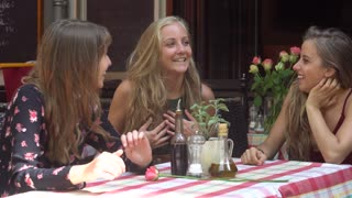 Three cute and young female friends at restaurant