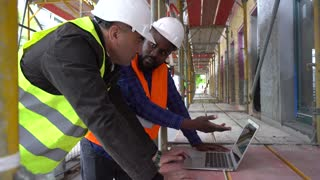 Tracking shot. Two engineers, a black and a white, wearing safety jackets and helmets, discussing looking at the computer among scaffolding