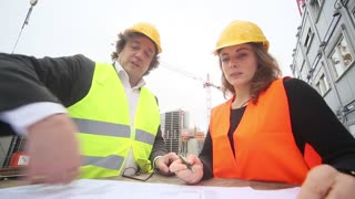 Two civil engineers, a man and a cute woman, working on drawings at construction site