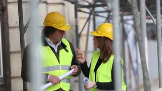 Two civil engineers inspecting the construction site and holding plans