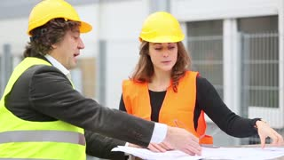Two construction engineers holding plans and inspecting the construction site