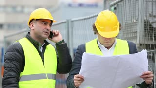 Two construction site managers discussing office blueprints at telephone