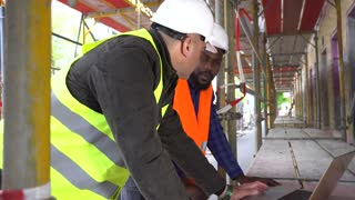 Two construction workers, a black and a white, wearing safety jackets and helmets, discussing looking at the computer among scaffolding. Tracking shot