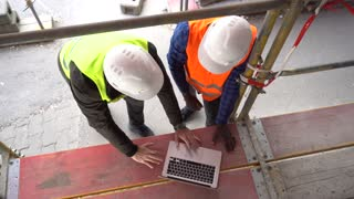 Two construction workers, wearing safety jackets and helmets, discussing looking at the computer among scaffolding. Overhead shot