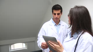Two doctors, a man and a woman, consult, check and discuss some clinical results looking at a digital tablet computer