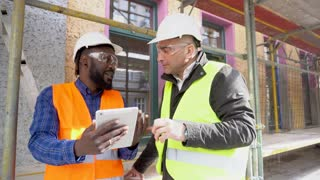 Two engineers, a black and a white, wearing safety jackets, helmets and goggles discussing and smiling looking at the computer among scaffolding