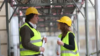 Two engineers, a man and a woman, wearing safety jackets and helmets, talking holding rolled office blueprints