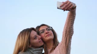 Two false blond girls taking selfie photo and laughing and giving five looking at the result. Outdoors