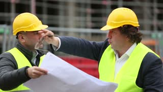 Two male construction site managers with hardhat discussing about technical drawings and pointing to scaffolding