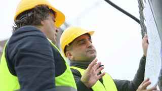 Two male construction workers discussing about office blueprints at construction site
