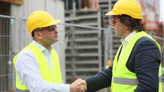 Two male engineers with safety yellow jackets and hardhats reaching an agreement on construction site
