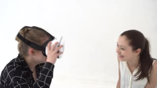 Two teenage girls sitting on the floor enjoying virtual reality experience wearing oculus rift