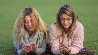 Two young women sitting on the grass using cell phones