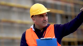 Absorbed civil engineer with protective workwear pointing upwards on construction site checking office blueprints
