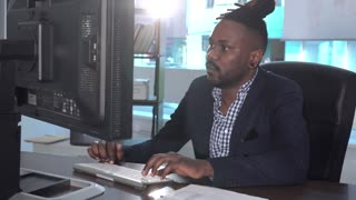 African American office worker at his desk working at computer receiving bad news. Pan