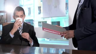 African American office worker bringing documents to his Asian boss sitting at desk