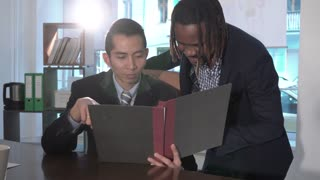 Asian and African American office workers reading paper documents at workplace. Pan