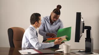 Asian manager in shirt and tie sitting at his workplace explaining documents to his African American assistant with collected rasta hair