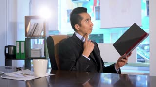 Asian manager sitting at his desk in office reading documents. Pan