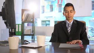 Asian manager sitting at his desk in office reading documents. Panning
