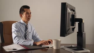 Asian white collar worker is sitting at his desk, typing on keyboard. Pan