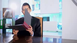 Asian white collar worker sitting at his desk in office reading documents. Pan