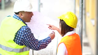 Back turned civil engineers wearing safety jacket and helmet reviewing office blueprints and technical drawings on construction site