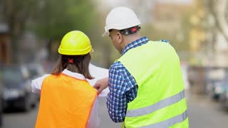 Back turned male and female civil engineers wearing protective workwear checking office blueprints and pointing to construction site. Outdoors