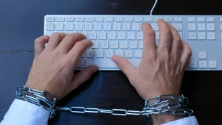 Businessman hands tied with chains on wrists typing on laptop keyboard