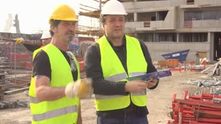 Civil engineer giving instructions to construction workers on construction site