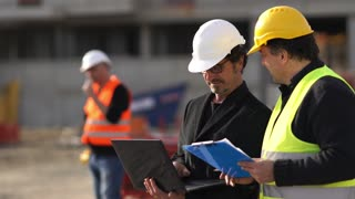 Civil engineer giving instructions to construction workers using a computer laptop. Outdoors