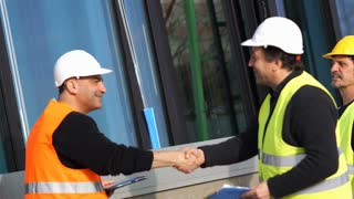 Construction manager and workers shaking hands on construction site