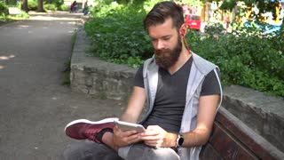 Cute guy with beard and earphones watching videos on a digitale e-reader tablet