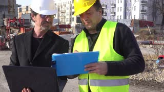 Elegant civil engineer giving instructions to construction worker using a computer laptop. Slow motion