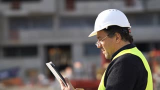 Engineer with safety vest and helmet checking plans on a digital tablet computer on construction site