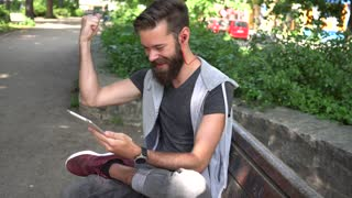 Exulting young man with raised arm celebrating reading something on his digital tablet