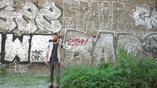 Handsome hipster guy with beard and earphones walking listening to music