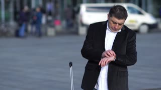 Impatient businessman checking the time and talking on mobile phone waiting for a delayed taxi. Outdoors