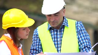 Male and female civil engineers wearing protective workwear checking office blueprints on construction site. Outdoors